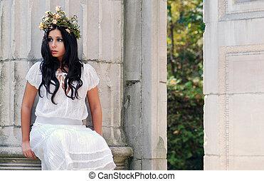 Young woman sitting on stone pillar