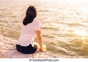 Young woman sitting on stone wall enjoying herself watching sunset at the beach