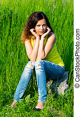 young woman sitting on stone