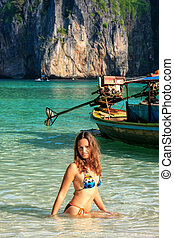 Young woman sitting on the beach at  Maya Bay on Phi Phi Leh Island, Krabi Province, Thailand