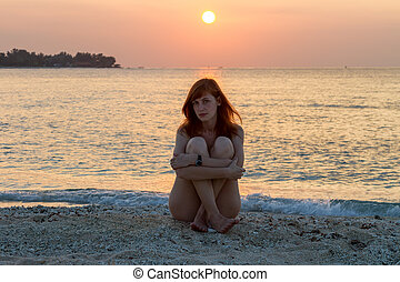 Young woman sitting on the beach at sunset