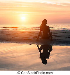 Young woman sitting on the beach during the amazing sunset. With the reflection in the water.