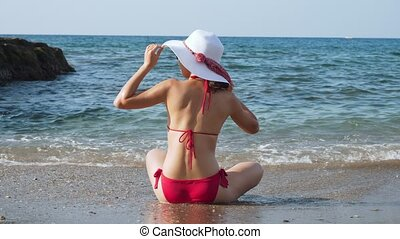 Young woman sitting on the beach in front of blue sea.