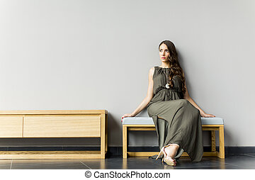 Young woman sitting on the chair in the room