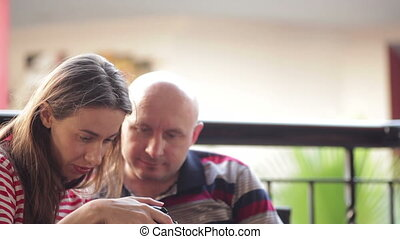 Young woman sitting on the couch with a man in the lobby and watch pictures on the camera