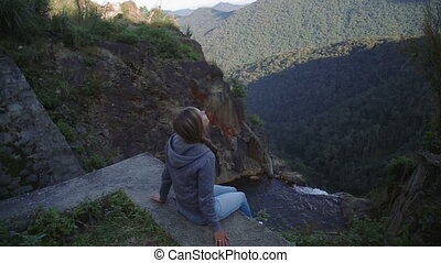 Young woman sitting on the edge of a rocky canyon above the river mountains vietnam
