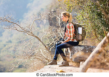 young woman sitting on the edge of cliff