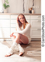 Young woman sitting on the floor in the kitchen