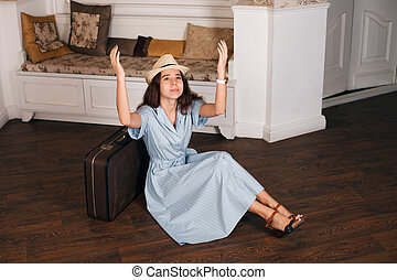 Young woman sitting on the floor nearby suitcase.