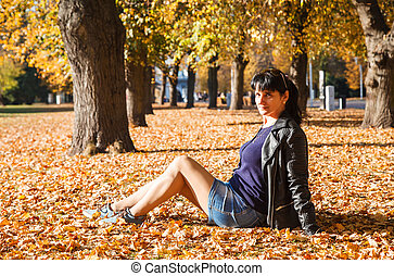 young woman sitting on the grass in the park in autumn