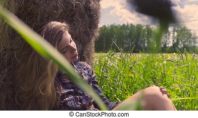 Young woman sitting on the grass near haystack