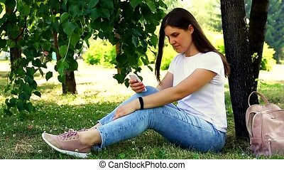 Young woman sitting on the grass with a mobile phone