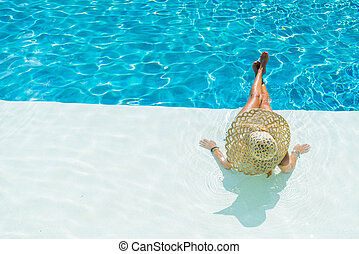 Young woman sitting on the ledge of the pool.