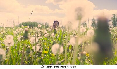 Young woman sitting on the meadow. Then she blowing...