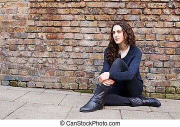 young woman sitting on the pavement