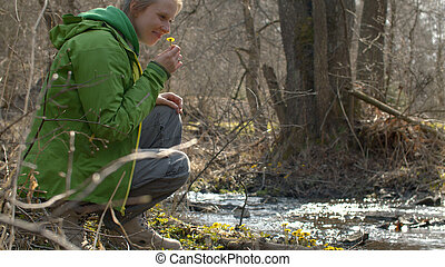 Young woman sitting on the river bank