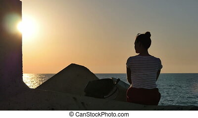 Young woman sitting on the rocks and looking at the sunset sea