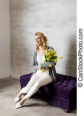 Young woman sitting on the sofa with a bouquet of yellow tulips