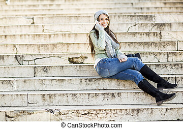 Young woman sitting on the stairs outdoor