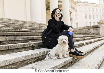 Young woman sitting on the steps with  small dog and using a mobile phone