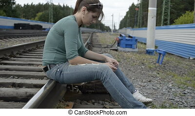 Young woman sitting on the tracks