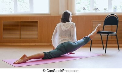 Young woman sitting on the yoga mat performing a split -...