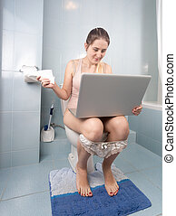 Young woman sitting on toilet and using laptop