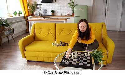 Young woman sitting on yellow sofa and playing chess in room. Female playing in logical board game with herself