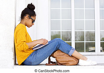 Young woman sitting outdoors and reading a book - Side view...