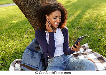 Young woman sitting outdoors in park using mobile phone listening music with earphones.