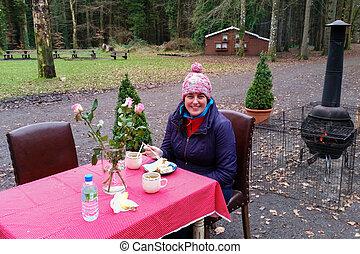 Young woman sitting outside enjoying carrot pie