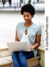 Young woman sitting outside working on laptop