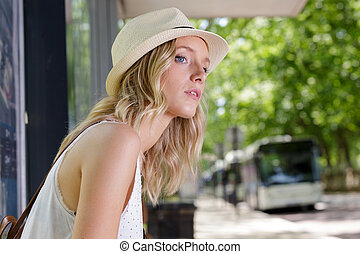 young woman sitting the bus stop