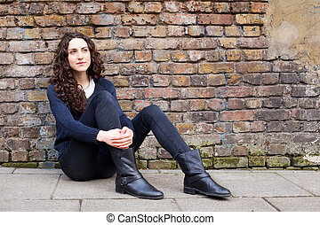 young woman sitting up against a brick wall