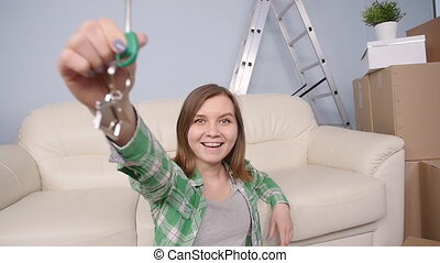Young woman sitting with cartons and holding keys to flat