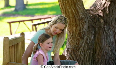 Young woman sitting with her sister on a bench