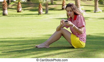 young woman sitting with phone