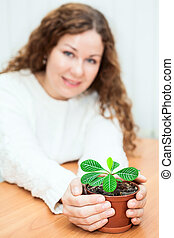 Young woman sitting with plant