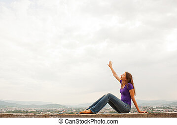 Young woman sitting with raised hand against blue sky