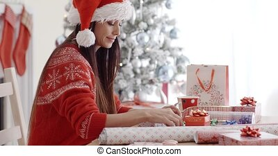 Young woman sitting wrapping Christmas gifts - Attractive...