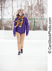 Young woman skating on ice with figure skates
