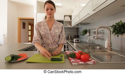 Young woman slicing a vegetable
