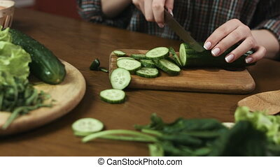 Young woman slicing green cucumbers for a salad with a knife , wooden board.