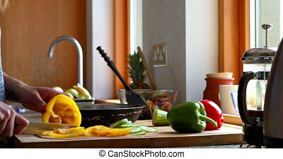 Young woman slicing peppers by the window at home in kitchen