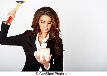 young woman smashed piggy bank with a hammer in a studio