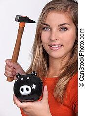 Young woman smashing her piggy bank