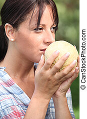 Young woman smelling a melon