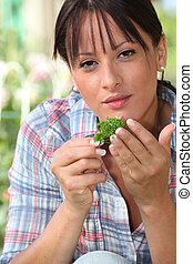young woman smelling a plant