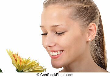 Young woman smelling a yellow flower