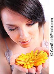 Young woman smelling an orange flower
